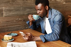 Young African man sitting at the coffee shop sending text message from his mobile phone. Student wearing trendy clothes, drinking coffee, using wireless Internet. Technology and communication concept