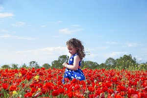 Girl playing in a field of poppies