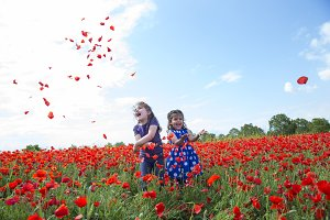 Girls playing in a field of poppies