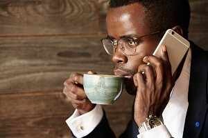 Young African businessman talking on mobile phone while working at the cafÈ. Young black corporate worker in glasses and formal suit making phone call while having coffee. Business and success concept