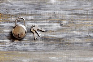 lock and key on blu wooden background