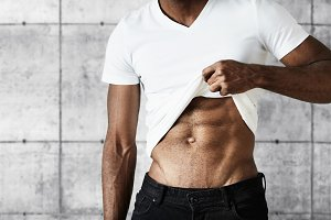 Cropped portrait of young black athletic man wearing black jeans and white T-shirt showing off his muscles. Attractive African male demonstrating his fit muscular body posing against gray brick wall
