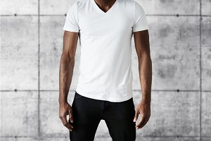 Cropped studio shot of dark skinned young male posing against white copy space wall wearing white T-shirt with copy space for your advertising content. T-shirt design and advertising concept.