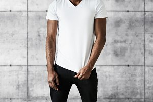 Cropped portrait of attractive African American man in trendy black jeans and white copy space T-shirt for your advertisement. Fit young black male posing against gray brick wall background