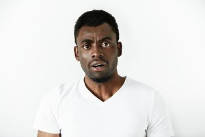 Headshot of puzzled black office worker in white polo shirt looking in shock and frustration at the camera after being told off by his boss. Human face expressions and emotions, body language