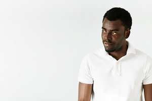 Handsome African American student wearing white polo shirt looking away with sad or disappointed expression, posing against white concrete wall with copy space for your text or advertising content