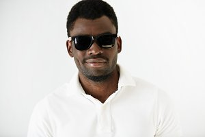Portrait of fashionable African American man wearing white polo shirt and stylish sunglasses, looking and smiling at the camera. Black bodyguard or secret agent. People and lifestyle concept