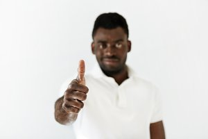 Portrait of positive handsome African male looking at the camera with confident smile, gesturing thumbs up, showing he likes and approves something, against white wall background. Selective focus