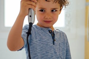 Child using a hair dryer at bathroom
