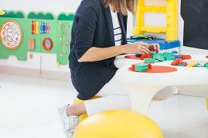 woman playing blocks at school