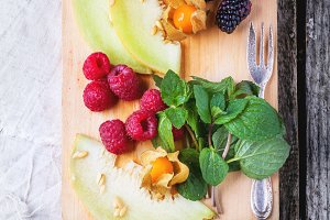 Berries, mint and melon on wooden cutting board