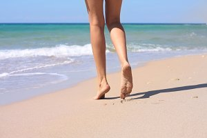 woman legs, sea and sand