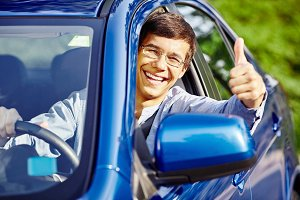 Guy inside car showing thumb up