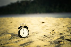 Alarm clock on morning sand beach