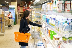 Young woman buying dairy or refrigerated groceries at the supermarket