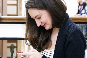 Happy girl using smartphone at cafe in shopping mall. Close-up of woman browsing information, scrolling pictures on smart phone and looking at camera