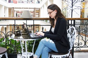 Young attractive woman in glasses are sitting at table in shopping mall and working on a laptop