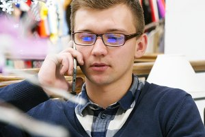 Young handsome man in glasses talking on the cellphone in shopping mall and working with laptop. Close-up