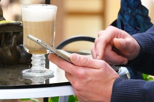 Male hands using smartphone and having cappuccino at cafe in shopping mall. Close-up of man browsing information and scrolling pictures on smart phone