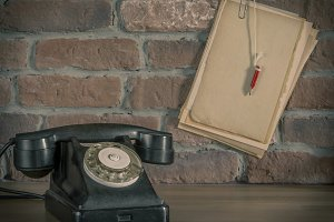Old telephone and paper with pencil