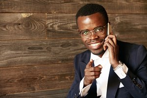 Portrait of handsome successful African businessman pointing a finger at you, looking and smiling at the camera while talking on smart phone with cheerful expression. Business and career concept