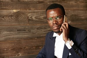 Successful young African corporate worker wearing formal suit and spectacles talking on mobile phone, looking with serious and confident expression at the camera. Business and career concept