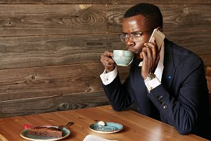 Successful young African CEO talking on the phone with serious and concentrated expression. Black student drinking cappuccino and having dessert, making phone calls while relaxing at the cafe