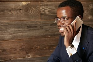 Portrait of African corporate worker wearing formal clothes talking on mobile phone with happy expression while sitting at the cafe against wooden wall background. Lifestyle and people concept