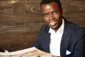 Isolated headshot of happy successful African American entrepreneur in spectacles and suit looking and smiling at the camera with confident cheerful expression against wooden wall background