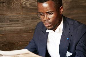 Portrait of young African entrepreneur in formal clothes reading financial newspaper with serious and concentrated expression before meeting with business partners. Lifestyle and people concept