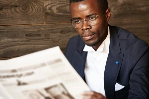 Close up portrait of serious black corporate worker in formal two-piece suit and spectacles holding newspaper and reading financial news with concentrated expression while having coffee at the cafe