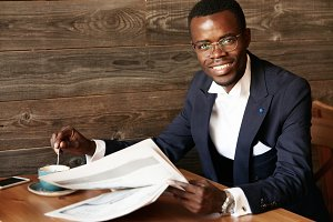 Young African entrepreneur wearing formal clothes and glasses looking and smiling at the camera, having coffee and looking through newspaper while sitting at the cafe. Success and achievement concept