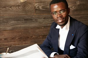 Lifestyle and people concept. Headshot of young African businessman in formal suit and glasses looking and smiling at the camera with confident and happy expression against wooden wall background
