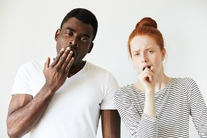 Mixed-race couple: African man standing next to his redhead Caucasian girlfriend, yawning, covering mouth. looking at the camera with tired and sleepy expression. Human face expressions and emotions
