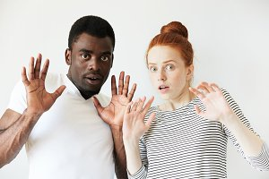 Interracial relationships. Caucasian female wearing striped top and African man in white T-shirt looking at the camera with scared and frightened face expression, holding hands up, with open mouth.