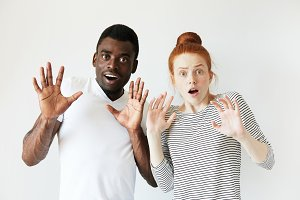 Handsome young African male and pretty redhead Caucasian woman looking at the camera with surprised and shocked expression, holding arms with open palms, frightened with something unexpected