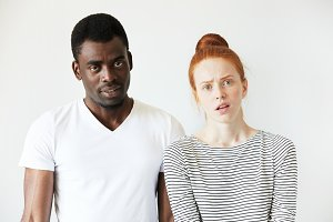 African man wearing white T-shirt standing next to his Caucasian girlfriend in sailor shirt, looking at the camera with disgusted and annoyed expression, quarrelling or breaking up. Human relations
