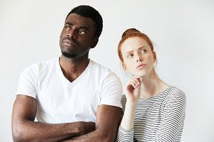 Interracial couple. Young redhead Caucasian female and African man in white T-shirt standing with arms folded against studio wall, not looking at each other, thing about divorce. Mixed-race relations