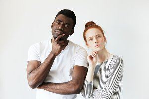 Portrait of sad mixed-race couple. Beautiful Caucasian woman with red hair and handsome African man, looking at the camera with unhappy offended expression, not speaking to each other. Body language