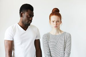 Extraordinary young interracial couple. Beautiful Caucasian woman looking at the camera with offended expression standing next to her boyfriend looking at her with angry and disappointed face