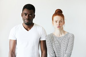 Interracial love and friendship. African male and redhead Caucasian woman looking at the camera with disappointment, having quarrel, displeased with each other. Portrait of young mixed-race couple