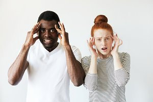 Portrait of irritated and annoyed young mixed-race couple. African man and Caucasian woman looking at the camera, holding hands on temples as if having headache. Human face expressions and emotions