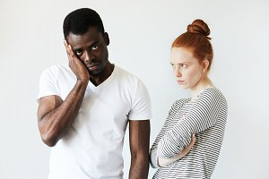 Portrait of young Caucasian female with red hair, standing with arms folded, angry and disappointed with her African boyfriend who looking at the camera with tired expression fed up with quarrelling