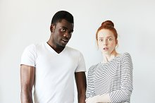 Young mixed-race couple: African man in white T-shirt and his redhead Caucasian girlfriend wearing sailor shirt, looking at the camera in shock and astonishment. Human face expressions and emotions