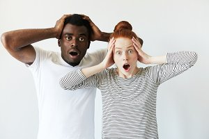 Surprised African male and redhead Caucasian female wearing casual clothes looking at the camera in shock, surprised with sale prices, holding hands on head, mouth wide open. Mixed race relationships