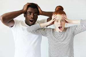 African man in white T-shirt and redhead Caucasian woman in striped top looking at the camera with surprised and shocked expression, holding hands on head. Isolated portrait of interracial couple