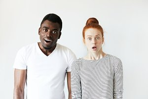 Interracial friendship. African man looking at the camera with surprised expression, standing next to his beautiful redhead Caucasian girlfriend, in full disbelief, shocked with some unexpected news.