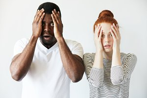Portrait of shocked interracial couple: African man and redhead Caucasian woman standing together against white wall, covering face, looking at the camera with scared and disappointed expression