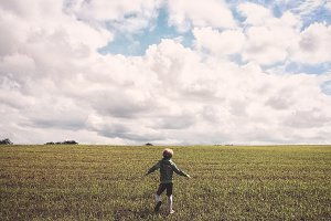 Boy Running in Grass