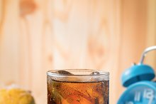 cola with ice cubes and bule clock